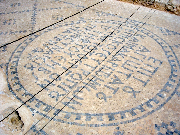 A Greek inscription, in tile mosaic, on the street.