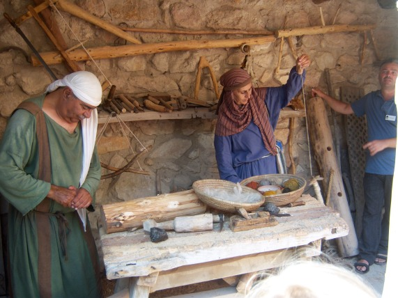 A carpenter demonstrates a few replicas of first-century woodworking tools, including a plane and a drill. The woman is showing how wool was spun into thread, to be woven on a loom.