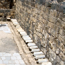 The bathhouse also included public (very public!) restrooms, pictured here. Guests must strategically perch between two jutting stones positioned over a trench, through which water would flow to carry away the refuse. Pretty sophisticated plumbing.